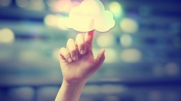 Hand pressing a cloud computing icon on blurred cityscape background