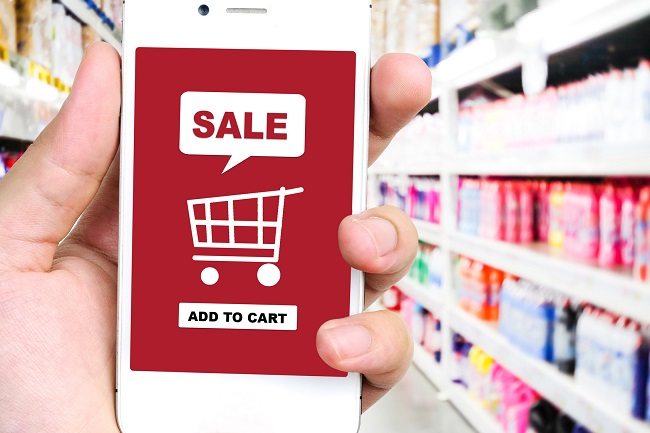 Sale and shopping on line concept on smart phone screen over blur supermarket background, e-commerce, business and technology concept