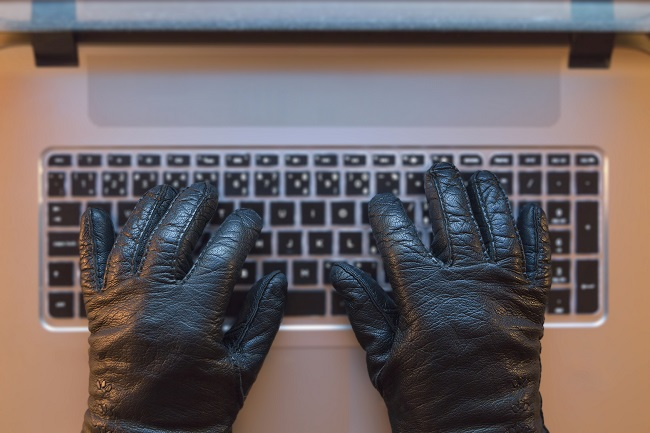 Computer crime metaphor, hand in black gloves on a computer.